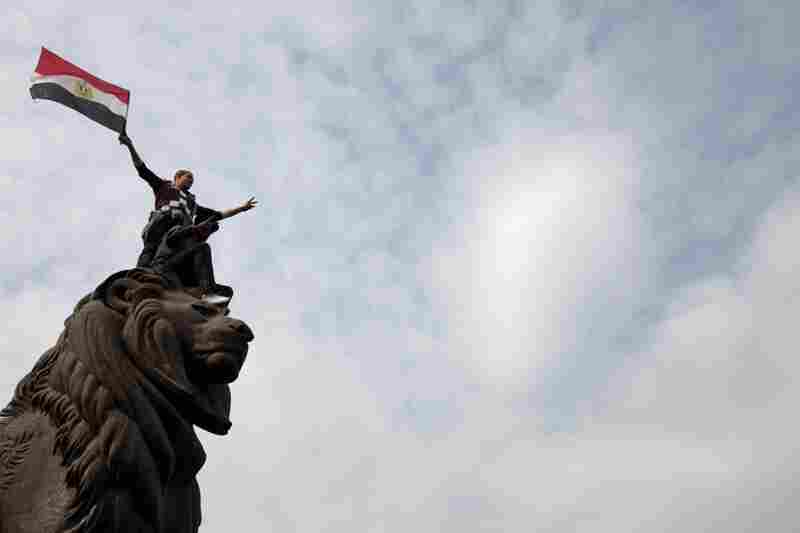 An Egyptian man waves the  national flag atop a sculpture during a protest in Cairo.