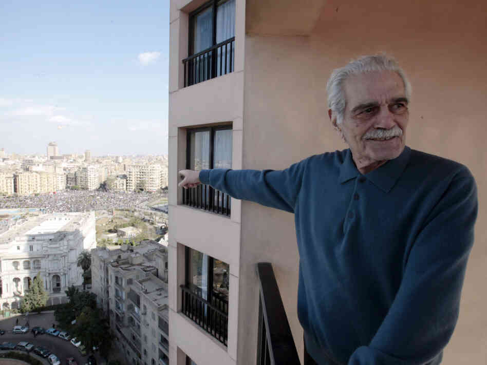Egyptian film star  Omar Sharif points to Tahrir, or Liberation, Square, in Cairo, Egypt, Monday Jan. 31, 2011. A coalition of opposition groups called for a million people to take to Cairo's streets Tuesday to demand the removal of President Hosni Mubarak. (AP Photo/Lefteris Pitarakis)