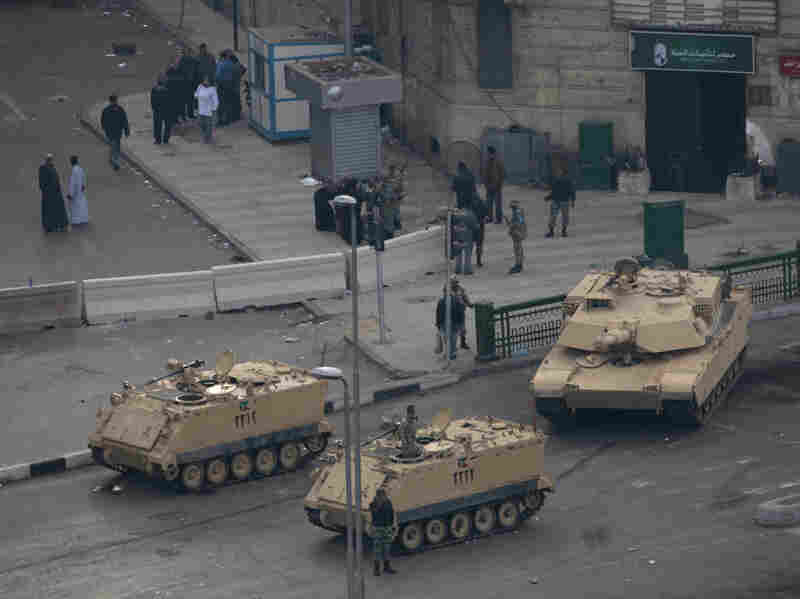 Egyptian military vehicles have surrounded Tahrir Square for days, keeping the protests confined but doing nothing to stop people from joining.