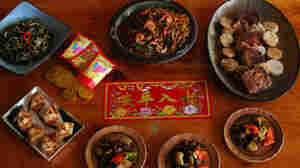 A wood table set with Chinese New Year decorations and a Trinidadian-Chinese feast, with wontons and stir-fried meats and noodles
