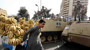 A vendor pulls his trolley past Egyptian army soldiers sitting and standing atop armored personnel  carriers in Cairo  on Saturday.