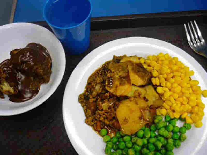 A 2010 school lunch in London, England of stew with groud beef and potatoes; peas; corn and pastry dessert.