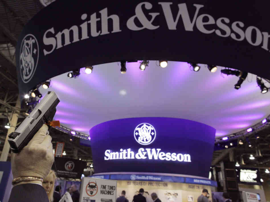 A retailer examines a Smith & Wesson hand gun at the Shooting, Hunting and Outdoor Trade show in Las Vegas, Jan. 18, 2011.