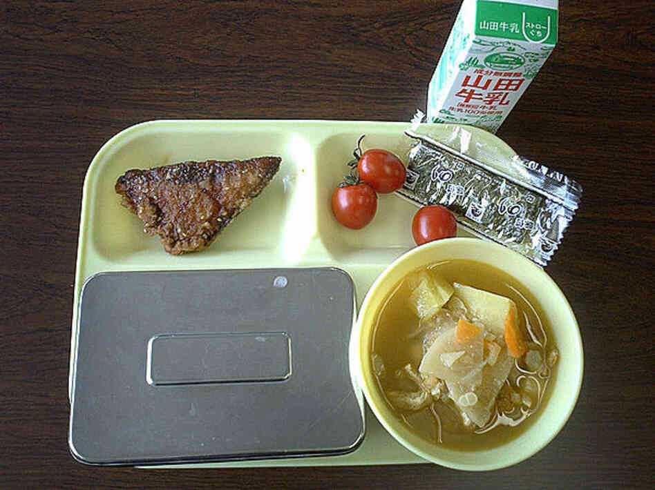Sendai, Japan, 2004. Fried fish, tomatoes, seaweed, milk, miso soup and rice in a metal container.