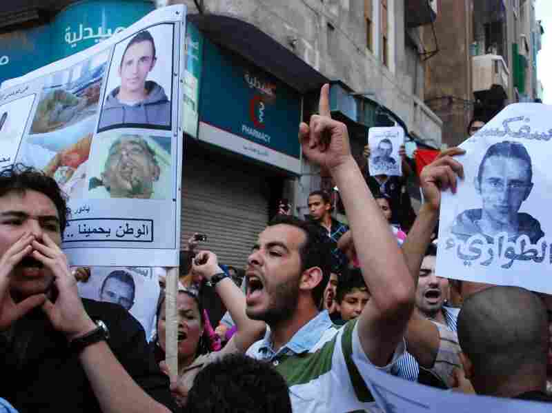 Egyptian protesters hold pictures showing slain  28-year-old Khaled Said  as they shout anti-police slogans during a  demonstration in Alexandria,  Egypt June 16, 2010.