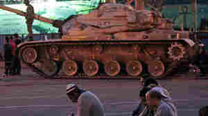 Anti-government  protesters offer their evening prayers in front of an Egyptian army tank securing the area during a protest Monday in Cairo's Tahrir Square.