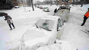 A car that plowed into a snow bank is towed Tuesday in Hartford, Conn. The latest storm is expected to add up to 6 more inches of snow and ice to an area already buried by multiple storms last month.
