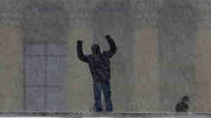 """A man has his photo taken by a companion at the top of the the so-called  """"Rocky Steps"""" in front of the Philadelphia Museum of Art during a blowing snowstorm Dec. 26. Philadelphia has been pounded by multiple heavy snowstorms this winter and has learned the terrible truth: Sometimes, weather hype is not hype at all."""