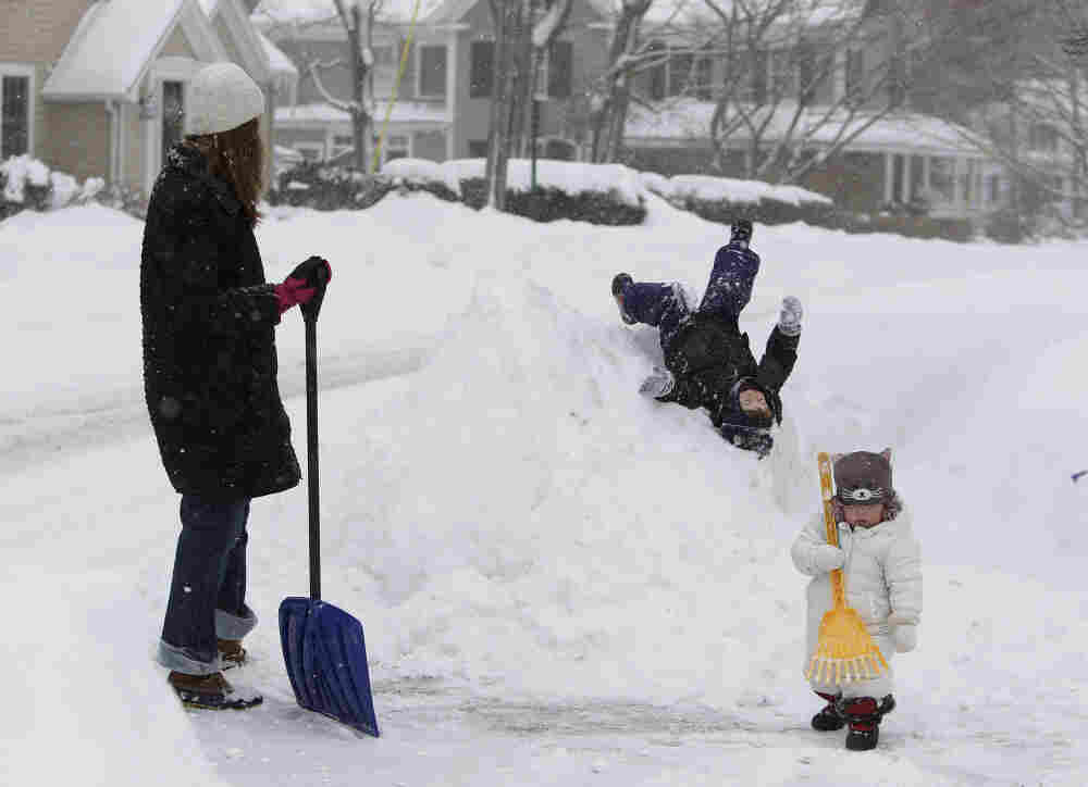 William Chisholm, 2, slides down a snow bank in front of his house as he mother, Tara looks on and his younger sister Ilona, 13 months, helps her mom shovel using a rake in Cohassett, Mass. The first half of a two-part winter storm is expected to drop up to a foot of snow in parts of New England Tuesday before a second storm slams into the area Wednesday.