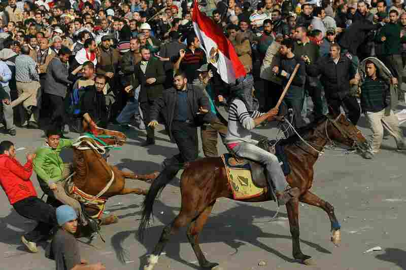 Supporters of Mubarak ride horses and wield sticks through the melee in Cairo's Tahrir Square.