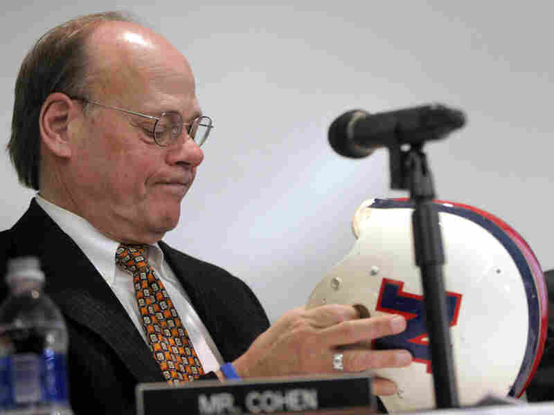 Steve Cohen, a member of the House Judiciary Committee, examines the helmet of Lem Barney, a former player for the Detroit Lions. A committee hearing last year evaluated steps taken at the professional, college and high school levels to deal with football brain injuries.