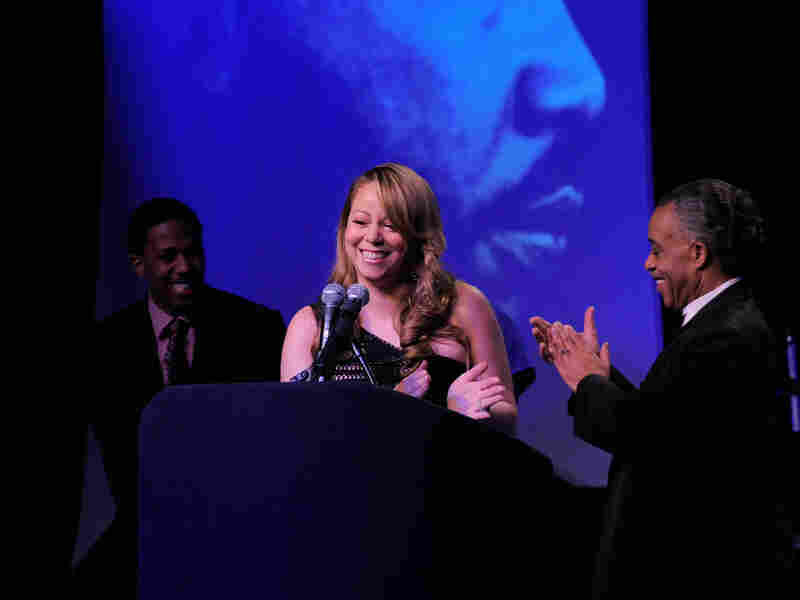 Singer Mariah Carey is joined on stage by her husband Nick Canon (L) and the Reverend Al Sharpton (R) as she receives the James Brown Cultural Excellence Award in New York in 2010.