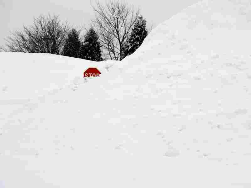 A stop sign pokes out of a large pile of snow at the end of a street in Enfield, Conn., on Tuesday.