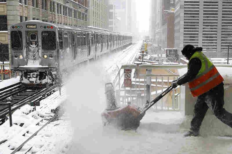 A Chicago Transit Authority employee removes snow from an elevated train platform during the blizzard Wednesday.