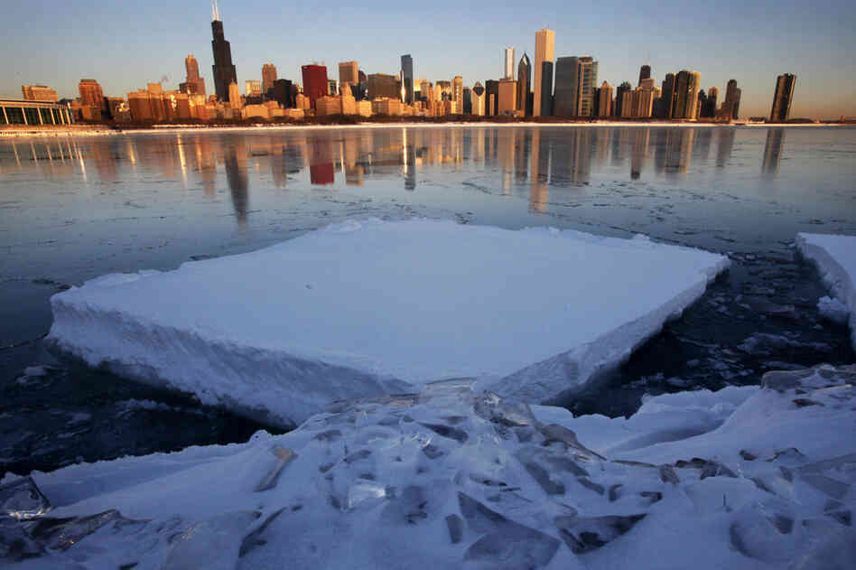 The Chicago skyline is reflected on a thin layer of ice in Monroe Harbor on Thursday, one day after a blizzard dumped the third largest snowfall in Chicago's history.