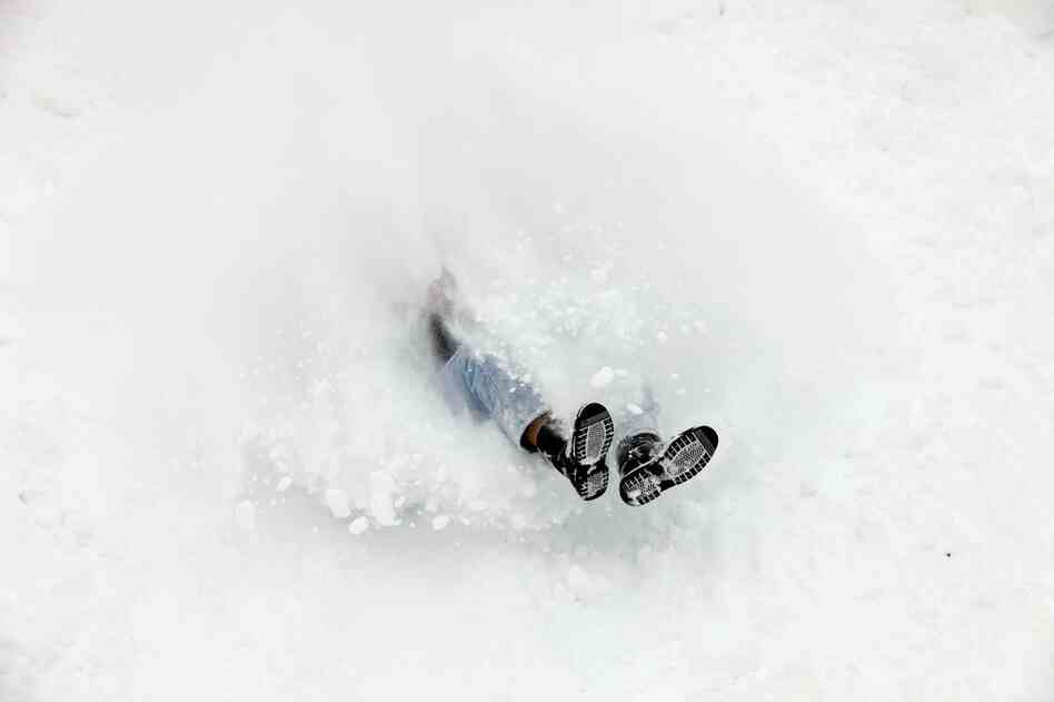 University of Iowa violin masters student Andrew Uhe uses a cookie sheet to sled down the hill behind Lincoln Elementary School on Wednesday in Iowa City, Iowa.
