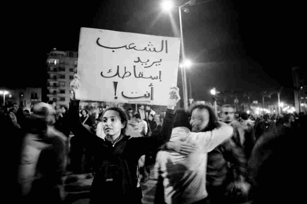 """A protester carrying a banner addressing Mubarak: """"The people want you to fall."""""""