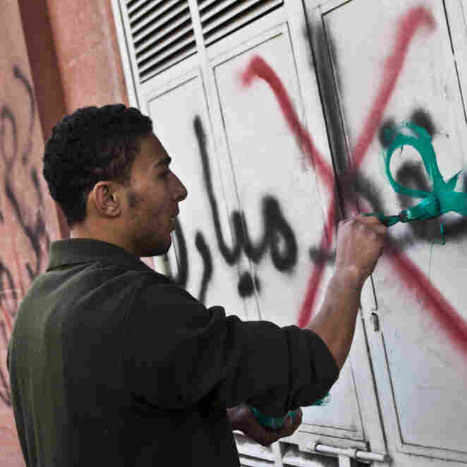 A pro-Mubarak supporter paints slogans over anti-Mubarak graffiti. This is the photo that Burton took right before he was attacked.