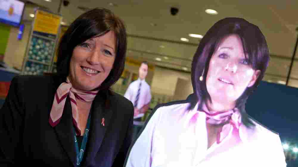 Julie Capper stands with her hologram at Manchester International Airport. Julie and her hologram work in the same area — which has created some confusion.
