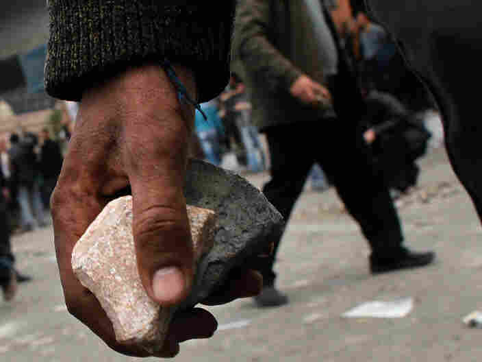Anti-government protesters carried rocks to throw at pro-government supporters near a highway overpass on the edge of Tahrir Square in Cairo earlier today (Feb. 3, 2011).