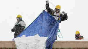 Workers remove snow from the roof of a Home Depot in Methuen, Mass., on Tuesday.
