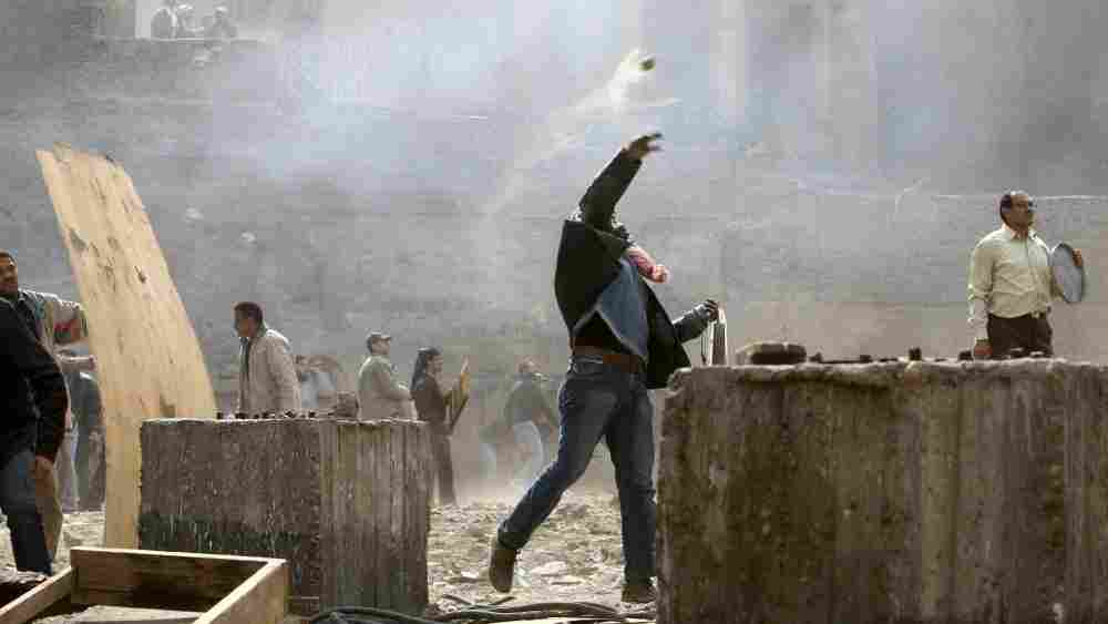 An Egyptian anti-government demonstrator battles pro-government opponents in Cairo's Tahrir Square on Thursday.