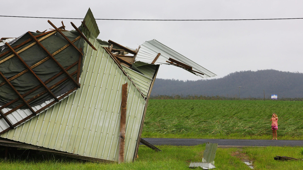 A local resident photographs a home on the outskirts of Innisfail, Australia, on Thursday after it was hit by Cyclone Yasi.