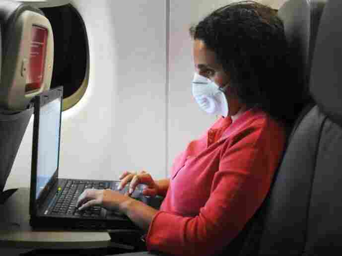 An airline passenger wears a mask to protect against viruses. Passengers are at risk of becoming infected in the airplane's cabin, just as they would be in any crowded, confined space.