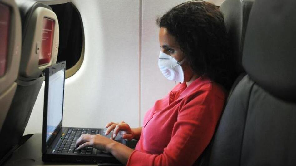 An airline passenger wears a mask to protect against viruses. Passengers are at risk of becoming infected in the airplane's cabin, just as they would be in any crowded, confined space. (AFP via Getty Images)