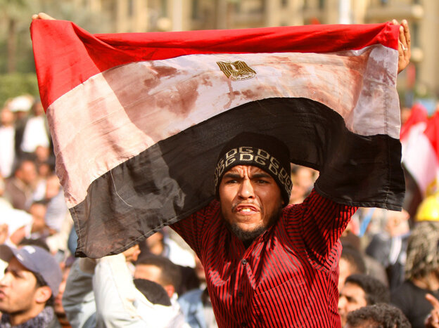 An protester waves a bloodstained Egyptian flag in Tahrir Square on Friday.