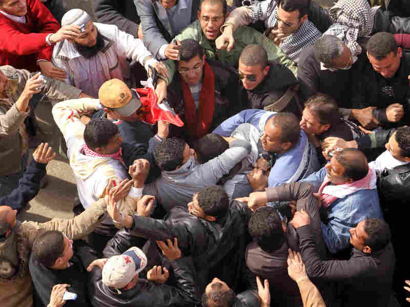 Egyptian protestors opposed to President Hosni Mubarak detain a government supporter during protests near Cairo's central Tahrir square. Some now wonder if past U.S. foreign aid to Egypt could have been handled in a better way to get Cairo moving toward democracy.