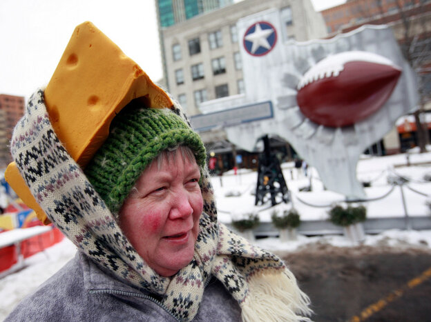 Caroline Fralia uses a scarf to secure her foam cheesehead hat Friday in Sundance Square in Fort Worth, Texas.