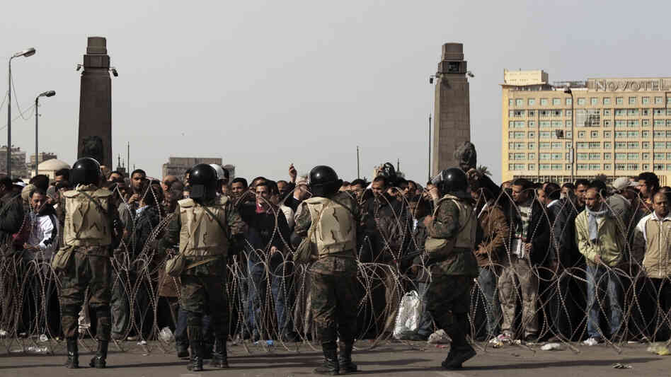 Egyptian soldiers stand behind barbed wire at the entrance of Cairo's Tahrir Square as anti-government demonstrators gather Friday.