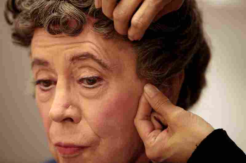 Nellie Laporte carefully slides Lady Bracknell's wig on over Bedford's wig cap.