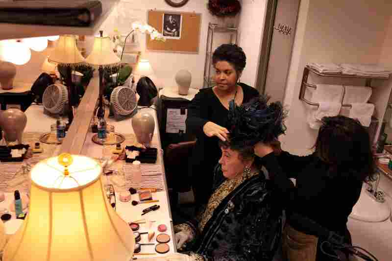 It takes two people to pin on Lady Bracknell's hat: Nellie Laporte and her assistant Yolanda Ramsay.