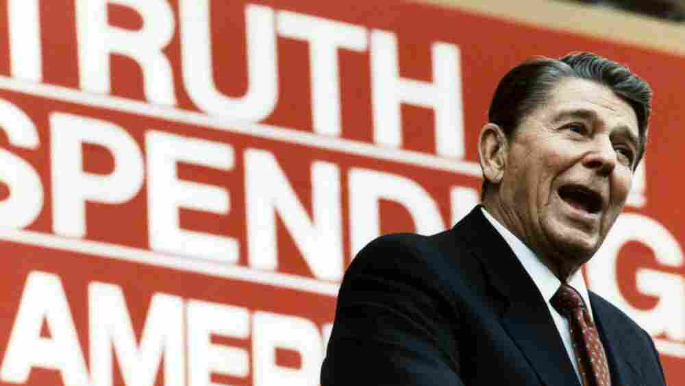 """President Ronald Reagan campaigns for his economic policies in 1987 before a sign that reads """"Truth in Spending, Americans Deserve It."""""""