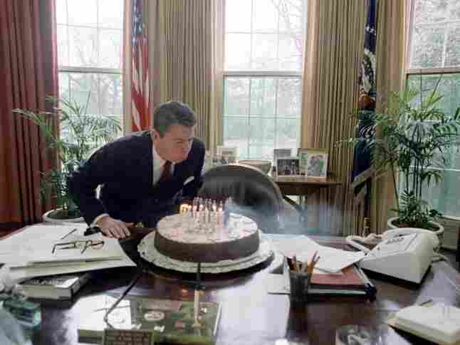 President Reagan blowing out candles on cake while celebrating his birthday in the Oval Office. Feb. 5, 1982.