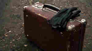 Old worn suitcase with gloves on a foggy country road.