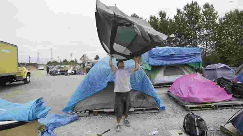 In July 2009, Ion Gardescu lifts up his tent to shake debris out as he breaks  camp at Nickelsville.