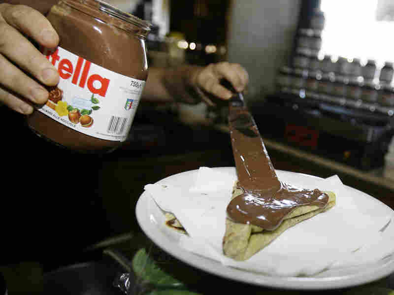 A bartender spreads Nutella on a crepe in a Rome creperie.