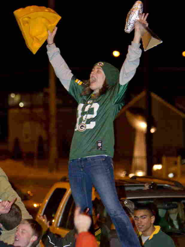 A Packers fan exults on the roof of a car in the middle of Green Bay's Lombardi Avenue on Sunday night after the Packers won Super Bowl XLV. She was one of the 111 million Americans who saw the game on TV, making it the most-watched TV show ever in the U.S.