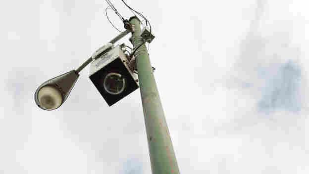 A new street surveillance camera in seen on top of a light pole along a street December 16, 2004.