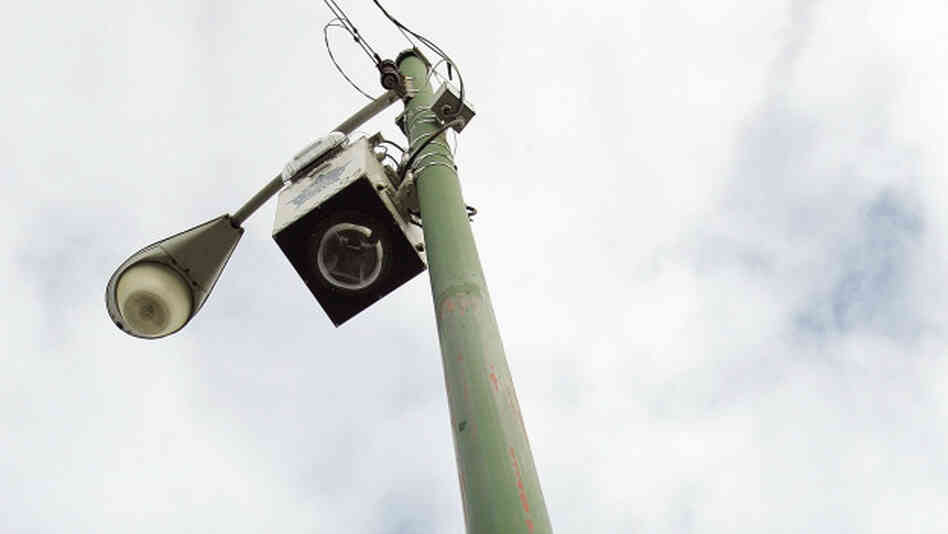 A new street surveillance camera in seen on top of a light pole along a street December 16, 2004.