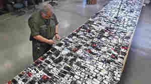 Correctional officer Jose Sandoval inspects one of the more than 2,000 cell phones confiscated from inmates at Calfornia State Prison, Solano, in Vacaville in 2009. One state lawmaker is trying to stiffen penalties for inmates found possessing a phone and for anyone caught smuggling one inside a California prison.