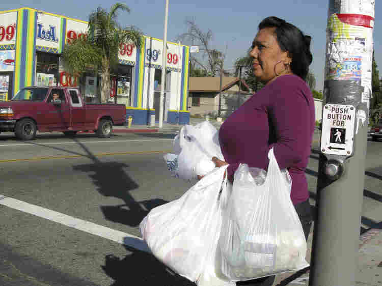 Loaded down with groceries, Olga Perez begins the journey back to her house. Her trip of nearly three miles will include a bus ride.