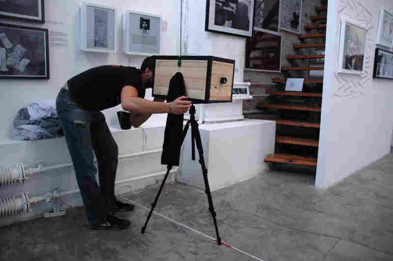 Birk peers through the open back of his box camera. To focus the camera, he moves a translucent glass plate toward or away from the lens until the image projected on the glass is sharp. This is where he will mount the photo-sensitive paper once the light is sealed out.