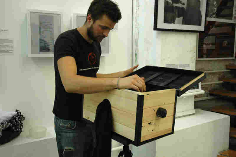 Birk and the first incarnation of his box camera, at an exhibition for some of his other work in Beijing in 2009. The black cloth hanging from the side covers a hole through which he can reach his hand to mount and develop the photo paper while preventing light from entering.