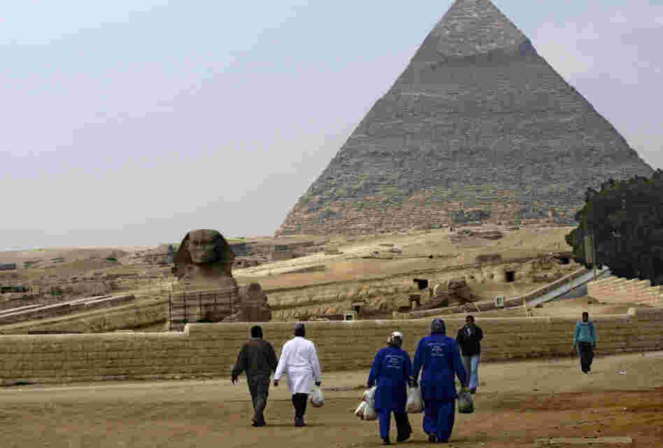 Street cleaners walk through the deserted pyramids site in Giza, one of Egypt's most famous tourist attractions, on Monday.