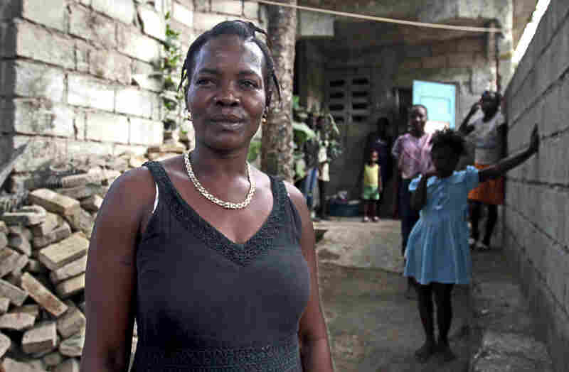 Marie Michel Noelsaint stands near her house; it wasn't demolished by the earthquake, but long cracks scar most of the walls.