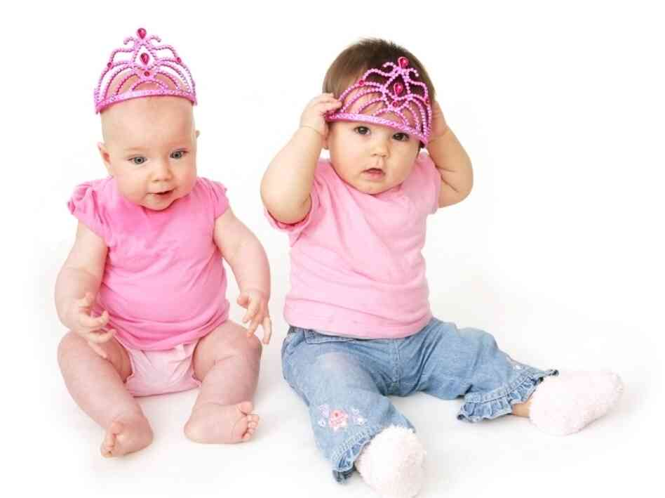 Infant girls wear pink T-shirts and matching tiaras.